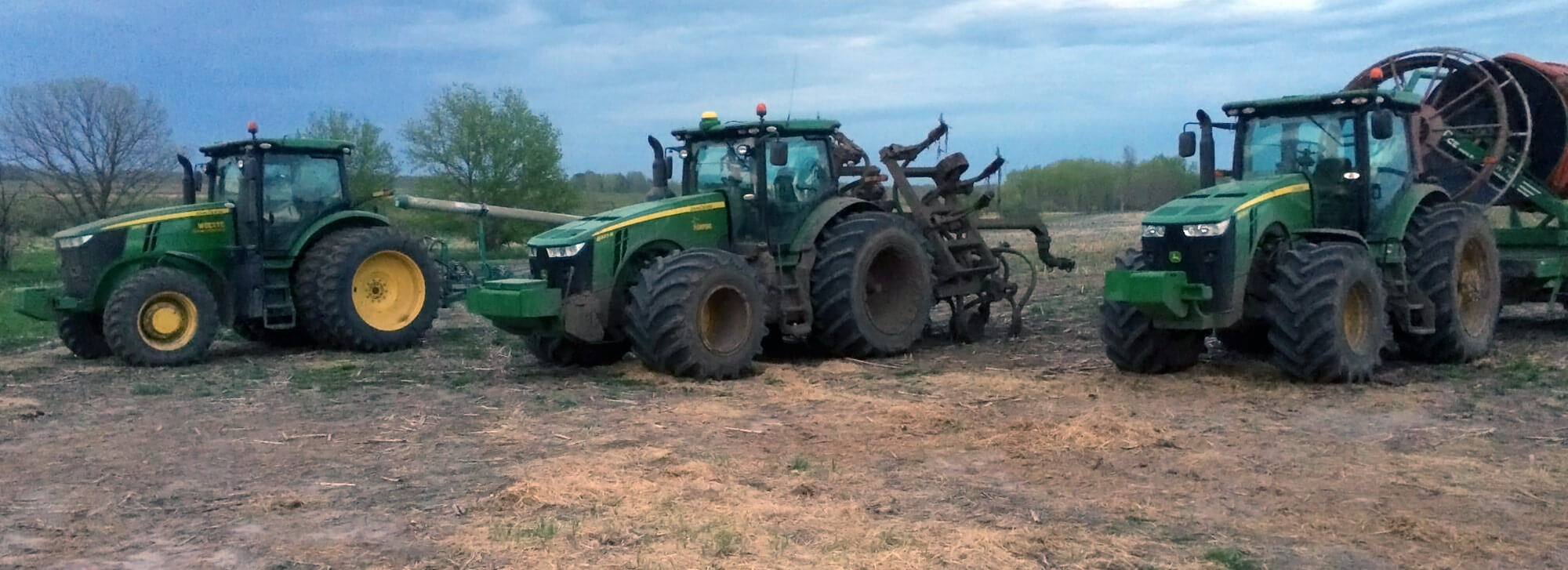 Group of John Deere tractors prepared for manure pumping via drag hose application